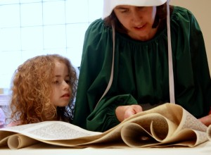 Woman in costume reading the megillah with her young daughter beside her, watching.