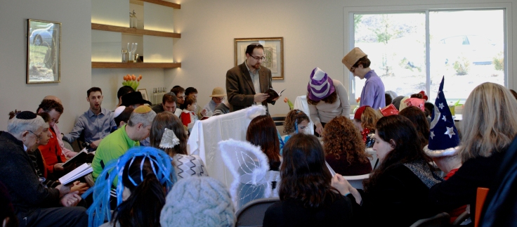 A daytime megillah reading in a living room, with men and women separated by a chest high mechitza and a table. At the table in the center a woman reads the megillah, with a male and female gabbai on either side, following along. Some adults and children are in costume. (sideview)