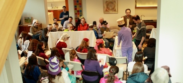 Top view of a megillah reading in a living room. Men and women are seated in a semi circle, and separated by a chest high mechitza and a table. At the table in the center a man reads the megillah, with a male and female gabbai on either side, following along. Some adults and children are in costume.